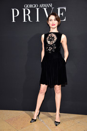 Olga Kurylenko went for flirty elegance in a Giorgio Armani velvet LBD with a lace-accented bodice when she attended the Armani Prive fashion show.
