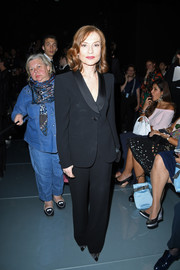 Isabelle Huppert donned a black suit with satin lapels for the Armani Prive fashion show.