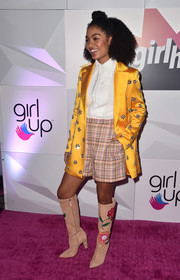 Yara Shahidi finished off her eclectic ensemble with a pair of knee-high floral boots by Carolina Herrera.