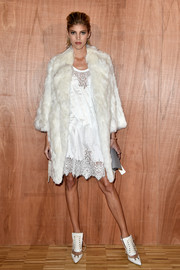 Devon Windsor layered a white fur coat over a lacy dress for the Givenchy fashion show.