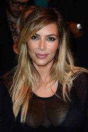 Kim Kardashian accentuated her post-pregnancy glow with a new blond layered hairstyle at the Givenchy fashion show.