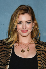 Anne Hathaway adorned her neck with a pair of gold pendants.
