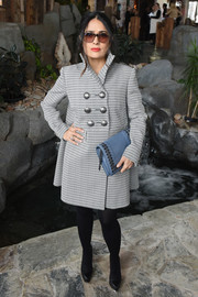 Salma Hayek paired her coat with a stylish blue leather clutch.