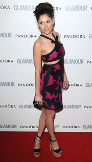 Eliza looks sweet in a black and fuchsia print dress with a bowed neckline and dramatic cutouts.
