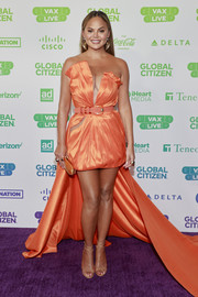 Chrissy Teigen made a head-turning entrance in a strapless orange dress with a high-low hem and a cleavage-baring illusion panel at the Global Citizen VAX LIVE.