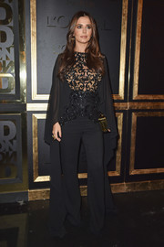Cheryl Cole vamped it up in a caped black jumpsuit with a sheer bodice at the Gold Obsession Party.