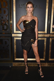 Hailey Baldwin hit the Gold Obsession Party wearing a deconstructed-chic strapless dress by Alexandre Vauthier.