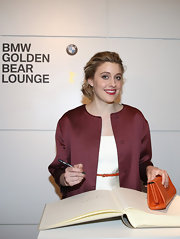 Greta Gerwig complemented her classy outfit with an orange leather clutch when she attended the Berlinale International Film Festival.