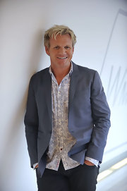 Gordon wears a cool slate gray blazer over a printed button-up.