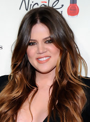 Khloe Kardashian wore a pop of gold coral lipstick at the Las Vegas opening of Kardashian Khaos.