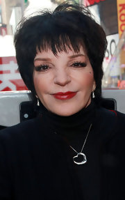 Liza Minnelli's interest in pendant necklaces showed as she wore a sterling heart at a ribbon cutting ceremony.