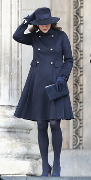 Kate Middleton completed her monochromatic look with a navy suede clutch by L.K.Bennett.