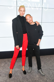 Karlie Kloss brightened up her black top with a pair of scarlet skinny pants.