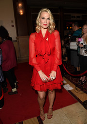 Molly Sims was ready for the holidays in this red tiered dress complete with sheer long-sleeves, a pussybow tie, and a ruffled hemline