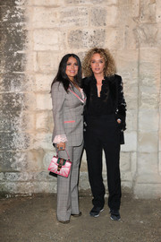 Salma Hayek teamed a crystal-embellished purse with a patterned pantsuit for the Gucci Cruise 2019 show.