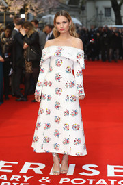 Lily James polished off her look with silver ankle-tie sandals by Jimmy Choo.