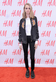 Cara Delevingne paired a tiger-embroidered bomber jacket with skinny jeans for the H&M Westfield World Trade Center opening.