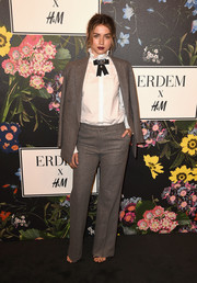 Ana de Armas stood out from a sea of floral dresses in her gray pantsuit and white ruffle-collar shirt combo at the Erdem x H&M runway show.