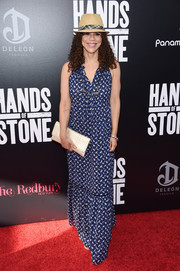 Rosie Perez paired her dress with a metallic gold clutch.