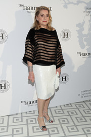 Catherine Deneuve attended the Harmonist Gala wearing a loose gold and black striped blouse.