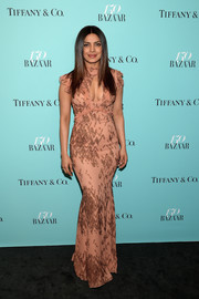 Priyanka Chopra cut a curvy silhouette in a fitted dusty-rose J. Mendel gown with a cleavage-baring cutout at the Harper's Bazaar 150th anniversary party.