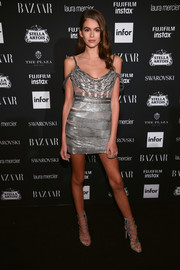 Kaia Gerber matched her dress with a pair of studded strappy heels.