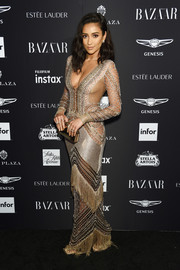 Shay Mitchell looked seductive in a gold Julien Macdonald knit gown with sheer panels and fringe detailing at the 2018 Harper's Bazaar Icons event.