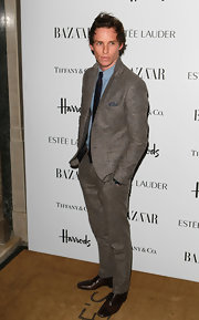 Eddie Redmayne looked cool and casual in a gray suit at the Harper's Bazaar Woman of the Year Awards.