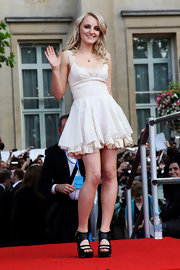 Evanna looks like a doll in a white ruffe and lace cocktail dress for the 'Harry Potter' UK premiere.