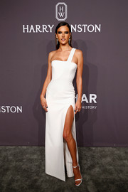 Alessandra Ambrosio looked simply divine in a high-slit white one-shoulder gown by Versace at the amfAR New York Gala.