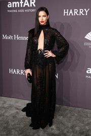 Adriana Lima burned up the gray carpet in a sheer black Zuhair Murad Couture gown with a cleavage-revealing cutout during the amfAR New York Gala.