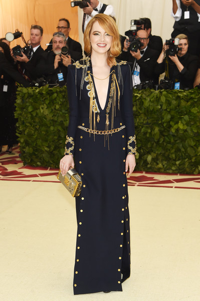 Emma Stone was military-glam in a chain-embellished navy gown by Louis Vuitton at the 2018 Met Gala.