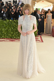 Anna Wintour looked queenly in an embellished cream Chanel gown with shoulder cutouts at the 2018 Met Gala.