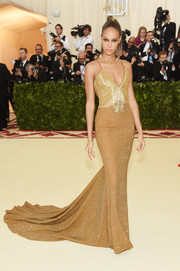 Joan Smalls chose a sparkling Tommy Hilfiger fishtail gown in two shades of gold for her 2018 Met Gala look.