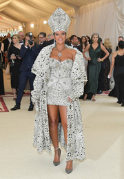 Rihanna sheathed her curves in an ornately beaded Maison Margiela mini dress with an attached overskirt for the 2018 Met Gala.