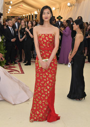 Liu Wen was svelte and chic in a strapless red Michael Kors gown with gold floral embellishments at the 2018 Met Gala.