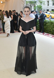 Lily Collins went goth in a sheer-bottom, off-the-shoulder gown by Givenchy Couture at the 2018 Met Gala.