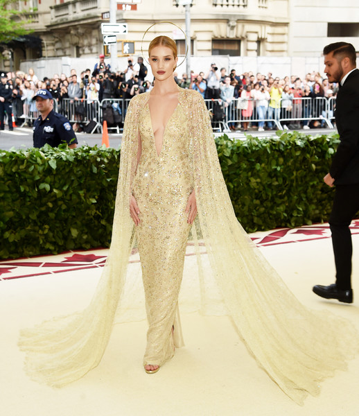 Rosie Huntington-Whiteley looked downright divine in a caped, Swarovski crystal-encrusted column dress by Ralph Lauren at the 2018 Met Gala.