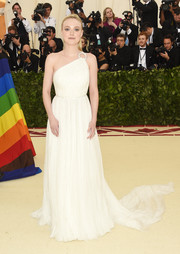Dakota Fanning looked angelic in a cream-colored one-shoulder gown by Miu Miu at the 2018 Met Gala.