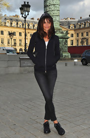 Helena Christensen posed for a Reebok event in a pair of the brand's all black sneakers. She paired the sporty shoes with cropped jeans and a black hoody.