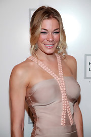 LeeAnn Rimes wore her hair in a loose ponytail to the Herve Leger Spring 2012 fashion show. To achieve her casual look, create a center part and section out some face-framing layers to curl with a medium-barreled iron. Pull the rest of the hair back into a low ponytail and secure with a hair elastic.