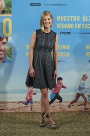 Rosamund Pike exuded youthful femininity in a mixed-pattern gray cocktail dress during the Madrid photocall for 'What We Did on Our Holiday.'