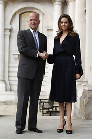 Angelina Jolie looked quietly elegant in this long-sleeve silk dress at a foreign office briefing.