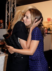 Natalie Portman attended a cocktail party where she showed off a quilted zip up Delices clutch.