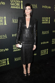 Deviating from her black motif, Paz Vega accessorized with a gold and white hard-case clutch by Rodo.