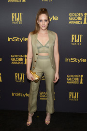 Carly Chaikin showed a bit of skin in a sleeveless olive-green pantsuit, which she wore open at the top to reveal a matching lace bra, during the HFPA and InStyle Golden Globe Award season celebration.