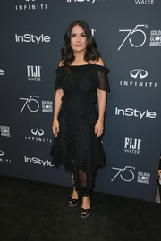 Salma Hayek was feminine and flirty in a ruffled black off-the-shoulder dress at the Golden Globes 75th anniversary celebration.