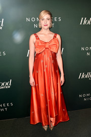 Greta Gerwig completed her eye-catching look with a pair of gold pumps.
