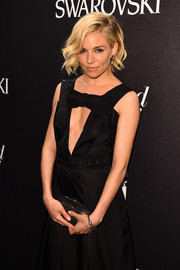 Sienna Miller styled her cutout dress with a shiny black clutch for the Hollywood Reporter & Swarovski party.