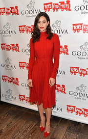 Emmy Rossum kept it conservative in a long-sleeve red midi dress by Ferragamo while hosting the Hot Chocolate for a Cause benefit.